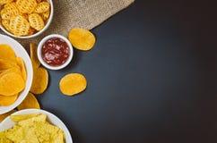 Patatas fritas y bocados en la tabla negra de la pizarra, visión superior imagen de archivo