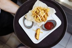 Patatas fritas y bolas de la patata con el tomate y la salsa blanca en una bandeja negra redonda en una tabla de madera fotos de archivo