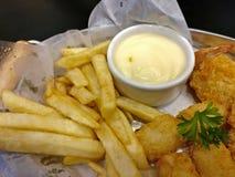 Patatas fritas y pepitas en plato Fotografía de archivo