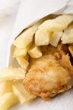 Patatas fritas y pescados en un bolso blanco Imagen de archivo