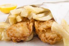 Patatas fritas y pescados en un bolso blanco Imágenes de archivo libres de regalías