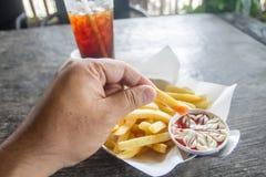 Patatas fritas y salsa de tomate con la tenencia de la mano Imagen de archivo libre de regalías