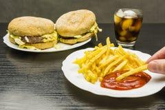 Patatas fritas y salsa de tomate en una placa y una hamburguesa y una cola con i imagen de archivo libre de regalías