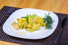 Patatas hervidas con las hierbas frescas en la placa blanca Imagen de archivo