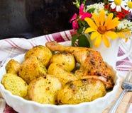Patatas hervidas en sus chaquetas y pollo quebradizo Imagen de archivo libre de regalías