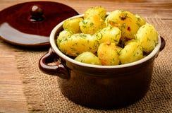 Patatas jovenes asadas con ajo y eneldo en fondo de madera marrón Fotografía de archivo