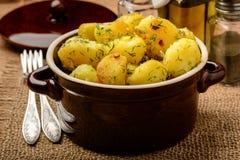 Patatas jovenes asadas con ajo y eneldo en fondo de madera marrón Imagenes de archivo