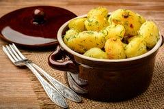 Patatas jovenes asadas con ajo y eneldo en fondo de madera marrón Fotografía de archivo libre de regalías