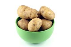 Patatas jovenes en un tazón de fuente verde aislado en blanco imagen de archivo