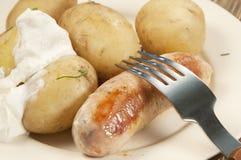 Patatas jovenes hervidas con la salchicha foto de archivo