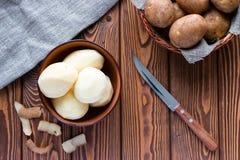 Patatas peladas al lado de la piel Foto de archivo