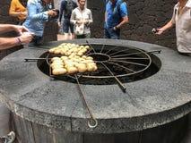 Patatas que cocinan sobre el horno de la lava Imagenes de archivo