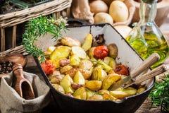 Patatas recientemente cocidas con los tomates, el ajo y el romero Fotografía de archivo