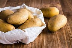 Patatas sin pelar crudas en el bolso Foto de archivo libre de regalías