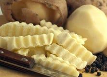 Patatas sin procesar y cuchillo Fotografía de archivo libre de regalías