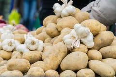 Patatas y ajo vendidos en el mercado Foto de archivo