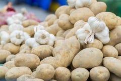 Patatas y ajo vendidos en el mercado Imagen de archivo libre de regalías