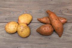 Patatas y patatas dulces en una tabla Imagen de archivo libre de regalías