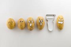 Patatas y policía asustadizos de la cara en el fondo blanco Imagenes de archivo