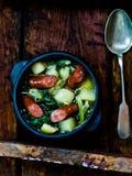 Patatas y salchicha en un pote Foto de archivo