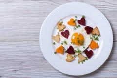 Patatas, zanahorias, remolachas y huevo fritos del corazón en una placa Fotos de archivo libres de regalías