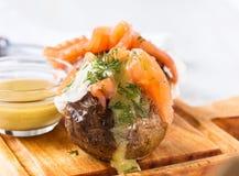 Patate bollite con la buccia con formaggio a pasta molle ed il salmone affumicato Fotografia Stock