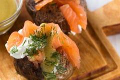Patate bollite con la buccia con formaggio a pasta molle ed il salmone affumicato Fotografie Stock Libere da Diritti