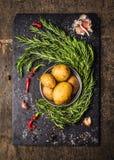 Patate con i rosmarini, l'aglio e le spezie, ingredienti crudi Fotografia Stock