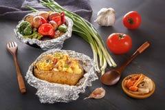 Patate cotte con bacon, le cipolle e le verdure al forno in stagnola - pomodori, melanzane, peperoni fotografia stock