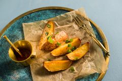 Patate cotte con le cipolle verdi, fondo bluastro fotografie stock libere da diritti
