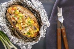 Patate cotte in stagnola con bacon, le cipolle ed i funghi con la coltelleria su una tavola di legno grigia fotografie stock libere da diritti