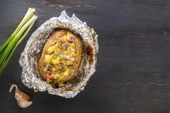 Patate cotte in stagnola con bacon, le cipolle ed i funghi su una tavola di legno grigia fotografia stock