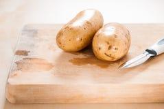 Patate crude sul tagliere con lo sbucciatore della patata Fotografia Stock