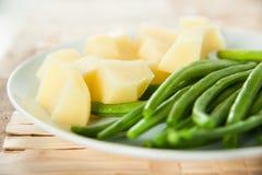 Patate cucinate senza pelle con i fagioli lunghi verdi fotografia stock