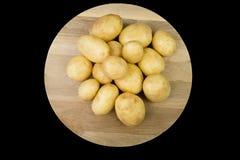 Patate dell'ayrshire su un bordo rotondo della quercia Immagini Stock