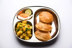 Patate della frittura O di Bombay di Aloo e puri/Poori in un piatto di ovale dell'acciaio inossidabile Immagini Stock