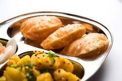 Patate della frittura O di Bombay di Aloo e puri/Poori in un piatto di ovale dell'acciaio inossidabile Fotografia Stock Libera da Diritti