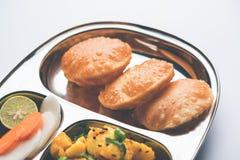 Patate della frittura O di Bombay di Aloo e puri/Poori in un piatto di ovale dell'acciaio inossidabile Fotografie Stock Libere da Diritti