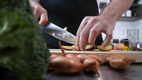 Patate di taglio del cuoco unico in cucina video d archivio