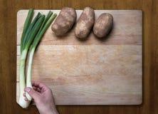 Patate e cipolle verdi sul blocchetto di spezzettamento Immagini Stock Libere da Diritti
