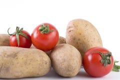 Patate e pomodori su un fondo bianco Patate su una priorità bassa bianca Fotografie Stock Libere da Diritti