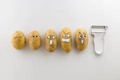 Patate e sbucciatore spaventosi del fronte su fondo bianco Fotografia Stock Libera da Diritti