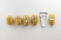 Patate e sbucciatore spaventosi del fronte su fondo bianco Immagini Stock