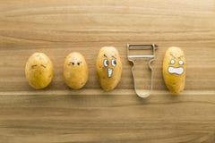 Patate e sbucciatore spaventosi del fronte sul tagliere di legno Fotografia Stock Libera da Diritti
