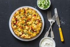 Patate e tortiglia su un fondo scuro, vista superiore delle verdure Le patate, fagiolini, peperoni dolci, piselli, formaggio, egg fotografia stock
