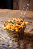 Patate fritte casalinghe con le cipolle fritte ed il cheddar fuso una tavola di legno immagine stock