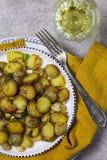 Patate fritte con i funghi e la cipolla in piatto bianco con la vite a fondo grigio per la cena di festa fotografia stock libera da diritti