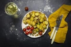 Patate fritte con i funghi, la cipolla ed i pomodori ciliegia in piatto bianco a fondo nero immagini stock libere da diritti