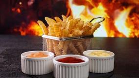 Patate fritte davanti alle fiamme del fuoco servite in piccolo canestro di frittura archivi video