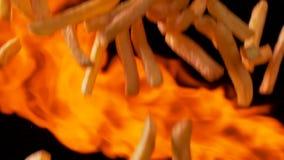 Patate fritte deliziose che cadono sul fondo delle fiamme video d archivio